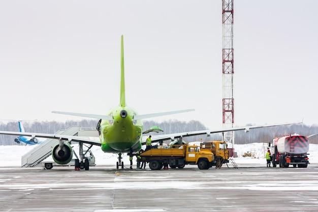 Bodenabfertigung des verkehrsflugzeugs im kalten winterflughafen