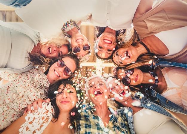 Bodenansicht von neun lächelnden frauen, die mit konfetti und lächeln einen geburtstag feiern. freundschaftskonzept. entspannung und glück für eine gruppe von menschen
