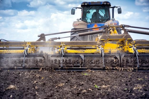 Bodenbearbeitung im feld mit einem traktor mit gezogener maschine.