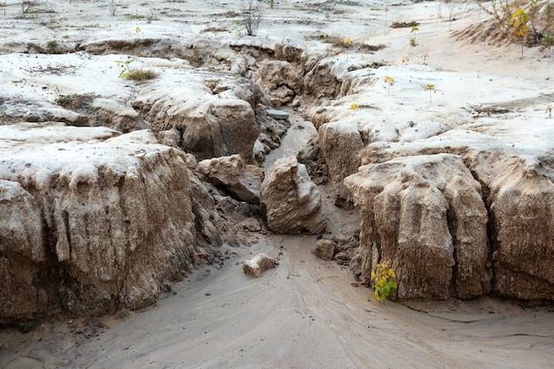 Bodenerosion, bildung von schluchten auf einem feld aufgrund von regenwasserabfluss, erdrutschen im sand und ökologischen problemen.