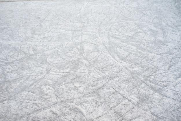 Bodenhintergrund einer gefrorenen eisbahn mit rochenmarkierungen, mit weißem schnee während des winters.