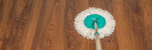 Bodenpflege, nassreinigung zu hause. waschen des braunen bodens mit einem runden mopp. platz kopieren