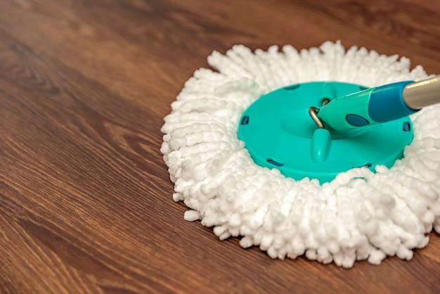 Bodenreinigung und desinfektion, hausnassreinigung. waschen des braunen vinylbodens mit einem runden mopp, hausreinigung, platz für text.