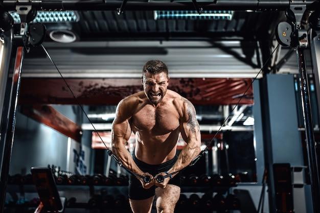 Bodybuilder arbeitet an seinem kasten mit kabel-überkreuzung in der turnhalle.