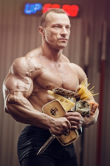 Bodybuilder athlet mit essen im fitnessstudio