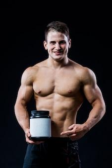 Bodybuilder, der ein schwarzes plastikglasleeres weißes aufklebermolkeprotein hält und auf es mit seiner hand lokalisiert auf dunkler wand zeigt