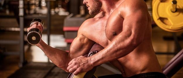 Bodybuilder, der im fitnessstudio mit hanteln trainiert. mann hebt hantel in einem fitnessstudio und macht übungen für die muskeln. mann-bodybuilder, der übungen mit hanteln macht. fitness-mann, der hantel hebt