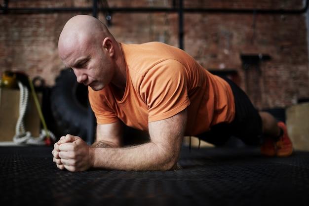 Bodybuilder, der in der planke steht