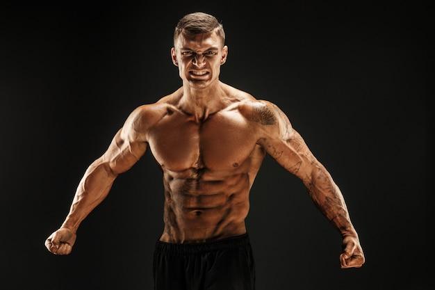 Bodybuilder, der mann mit muskeln der eignung auf der dunklen szene brüllt für motivation aufwirft