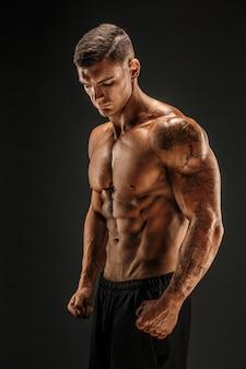 Bodybuilder, der mann mit muskeln der eignung auf dunkler szene aufwirft