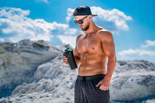Bodybuilder, der proteinerschütterung nach dem trainieren stillsteht und trinkt. sport im freien.