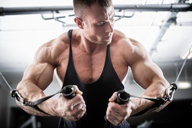 Bodybuilder, der schmetterling auf seilzug tut