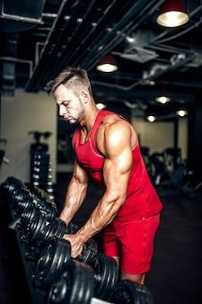 Bodybuilder, der schwere schwarze dummköpfe an der turnhalle anhebt.