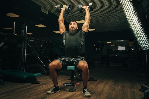 Bodybuilder, der übungen mit hanteln in einem dunklen fitnessstudio macht