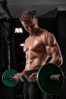 Bodybuilder, der übungen mit langhantel in der turnhalle macht starker athletischer mann zeigt körperbauchmuskeln