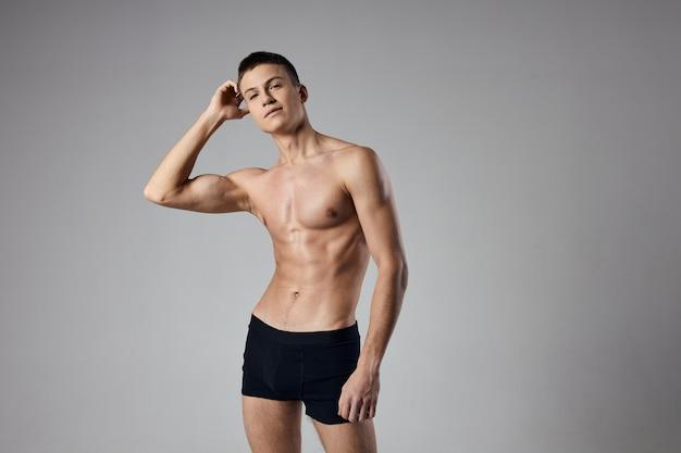 Bodybuilder in schwarzen shorts hält die hand in der nähe des gesichts