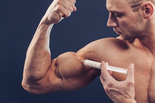 Bodybuilder injiziert vitamine. foto des sportlichen mannes mit perfektem körperbau auf dunklem hintergrund. kraft und motivation