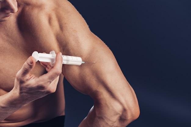 Bodybuilder macht injektion von vitaminen foto des sportlichen mannes mit perfektem körperbau auf dunklem hintergrund