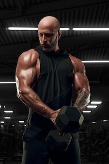 Bodybuilder männliches modell training bizeps muskeln mit hantel. modell im schwarzen hemd
