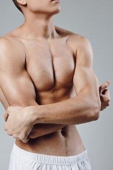 Bodybuilder mit aufgepumpten bauch- und armmuskeln bizeps sportler fitness