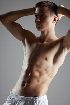 Bodybuilder mit einem aufgepumpten oberkörper, der seine hände hinter seinem kopf auf einem grauen hintergrund hält, abgeschnitten