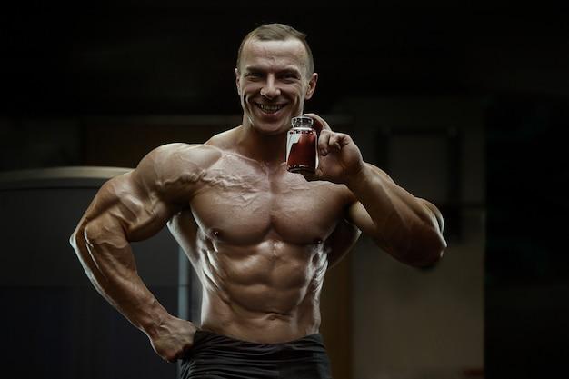 Bodybuilder mit proteinpulver ergänzt glas
