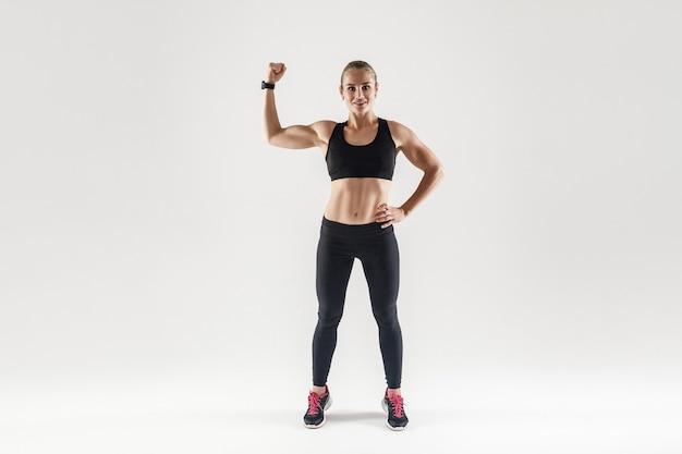 Bodybuilder, muskulöses mädchen engagierte fitness. frau, die ihren bizeps in die kamera zeigt und lächelt. studioaufnahme, grauer hintergrund