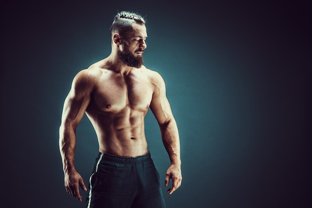 Bodybuilder posieren. mann mit muskeln der eignung auf dunklem hintergrund.