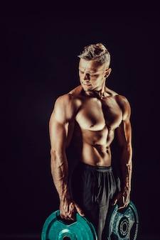 Bodybuilder posiert mit hanteln