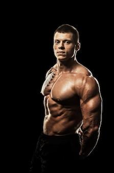 Bodybuilder posiert. schöne männliche kraft des sportlichen kerls. fitness mus