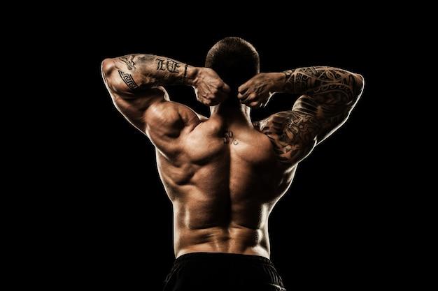 Bodybuilder posiert. schöne männliche kraft des sportlichen kerls. fitness