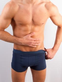 Bodybuilder posong. männliche energie des schönen sportlichen kerls. fitness bemuskelt mann