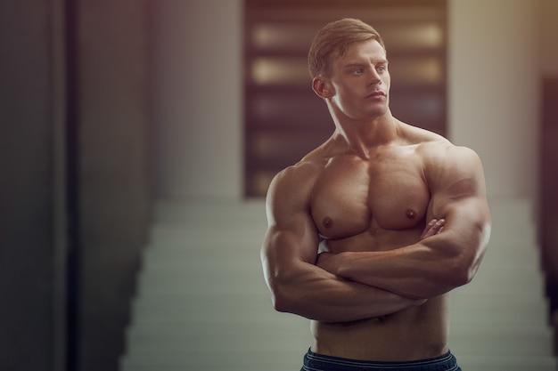 Bodybuilder schöner starker athletischer rauer mann, der muskeln aufpumpt