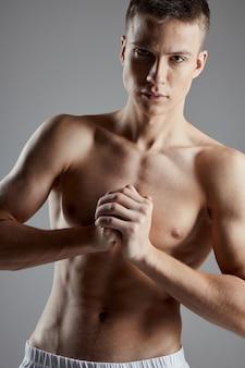 Bodybuilder verband sich die hände in der nähe der brust auf grauem hintergrundkopierraum
