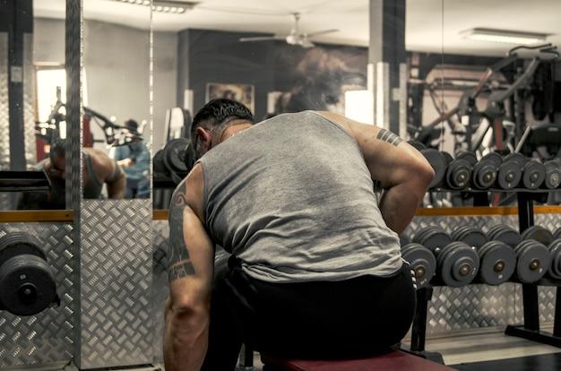 Bodybuilder zurück vom mann im schweißt-shirt bereiten sich für neues training in der turnhalle vor