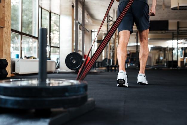 Bodybuildertraining mit last im fitnessstudio. abgeschnitten