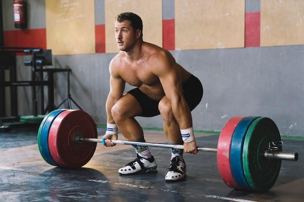Bodybuilding-konzept mit mann im fitnessstudio heben hantel