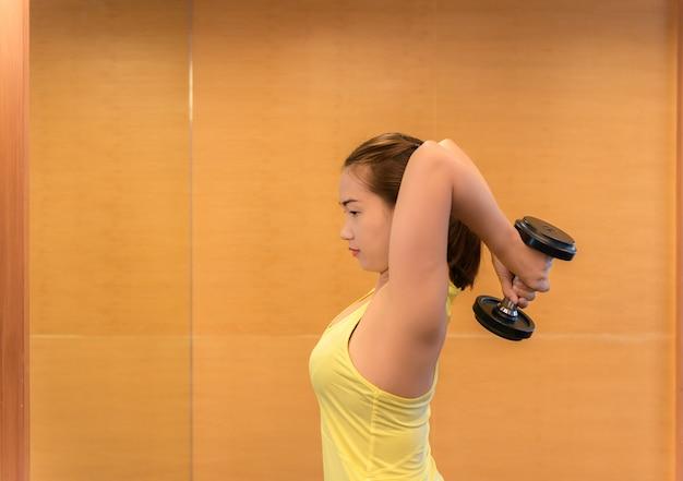 Bodybuilding. starke sitzfrau, die mit dummköpfen trainiert.