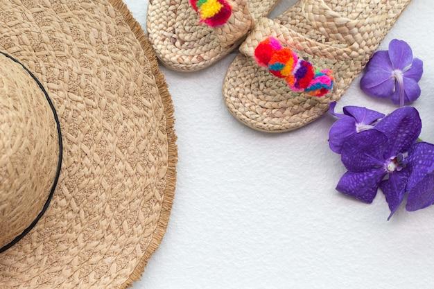 Böhmischer strohweidenhut und pantoffel mit purpurroter orchidee. boho stil modell.