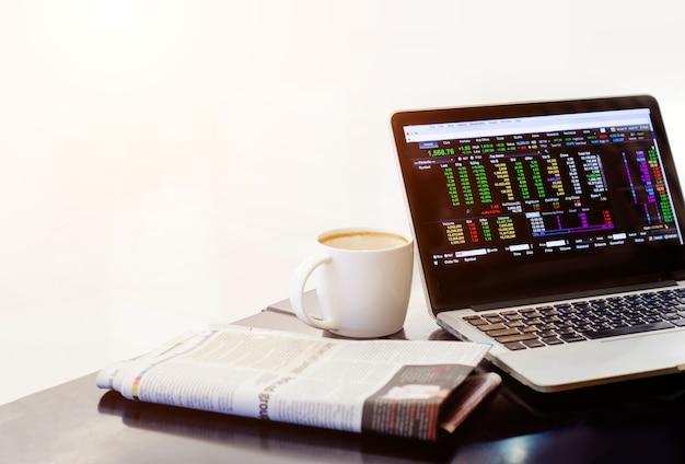 Börse in notebook mit zeitung und kaffeetasse