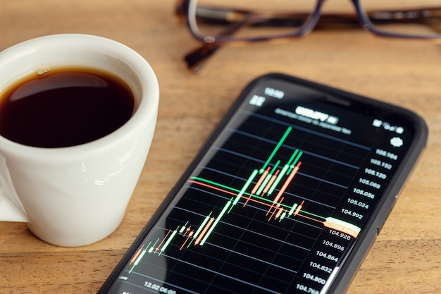 Börsenhandel auf tragbarem gerätekonzept. diagramm auf dem smartphonebildschirm auf dem schreibtisch. handels- oder anlagekonzept
