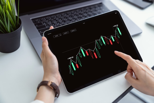 Börseninvestitionen, digitales tablet mit handpresse und das handelsdiagramm am arbeitsplatz zur bewertung des marktwerts.