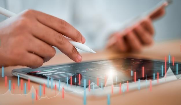 Börsenkonzept, geschäftsmannhändler, der auf tablette mit grafikanalyse-kerzenlinie im büroraum, diagramme auf bildschirm schaut.