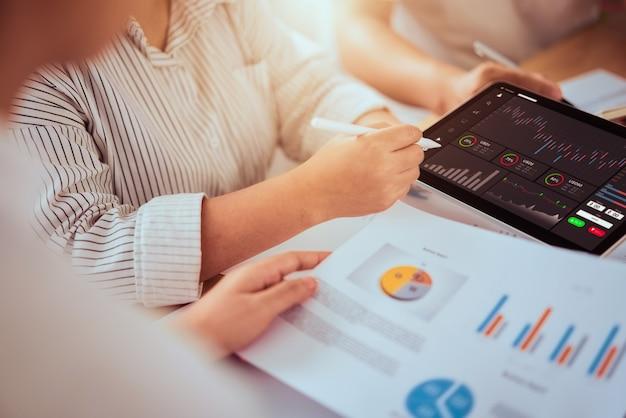Börsenkonzept, geschäftsmannhändler und team, die auf tablette mit grafikanalyse-kerzenlinie im büroraum, diagramme auf dem bildschirm suchen.