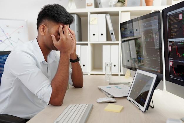 Börsenmakler, der die augen mit den händen bedeckt, wenn er gestresst am tisch sitzt, nachdem er viel geld verloren hat