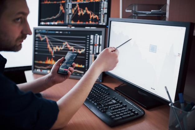 Börsenmakler im hemd arbeitet in einem überwachungsraum mit bildschirmen. börse, die devisen-finanzgraphik handelt. geschäftsleute, die online mit aktien handeln