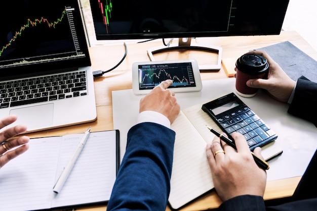 Börsenmaklerteam diskutieren mit bildschirmen analysieren von daten