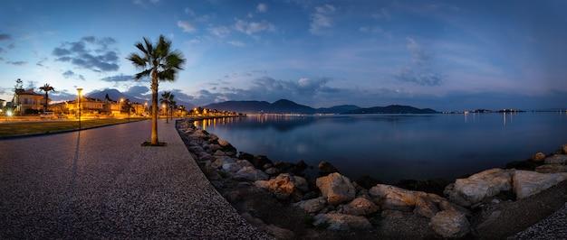 Böschung mit einem weg und palmen, die am frühen morgen von laternen beleuchtet werden. panorama. fethiye, türkei