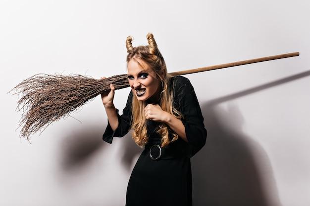 Böse hexe, die lustige gesichter auf weißer wand macht. innenfoto des blonden vampirmädchens.