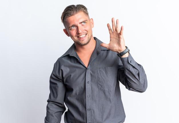 Böser fröhlicher blonder gutaussehender mann, der mit erhobener hand nach oben schaut